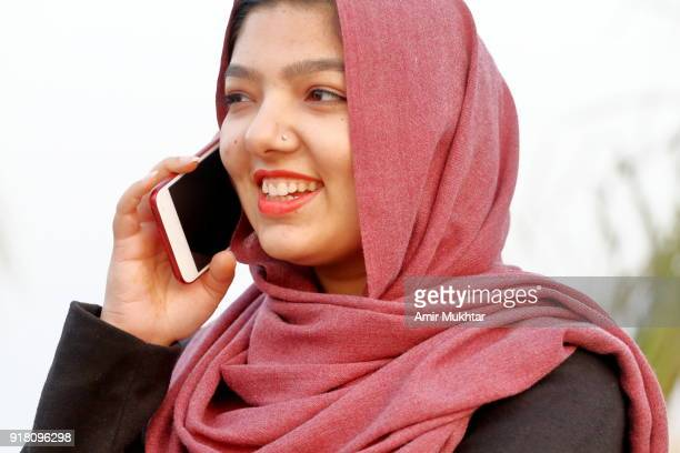 a young girl in hijab (head scarf) talking on cell phone - pakistan girl stock photos and pictures
