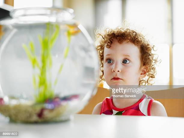 Young girl in home looking at fish in fishbowl