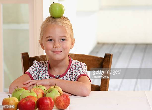 Young girl in kitchen balancing apple on her head smiling