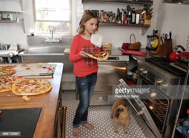 """""""young girl in kitchen, putting pizza in oven"""" - girls barefoot in jeans stock photos and pictures"""
