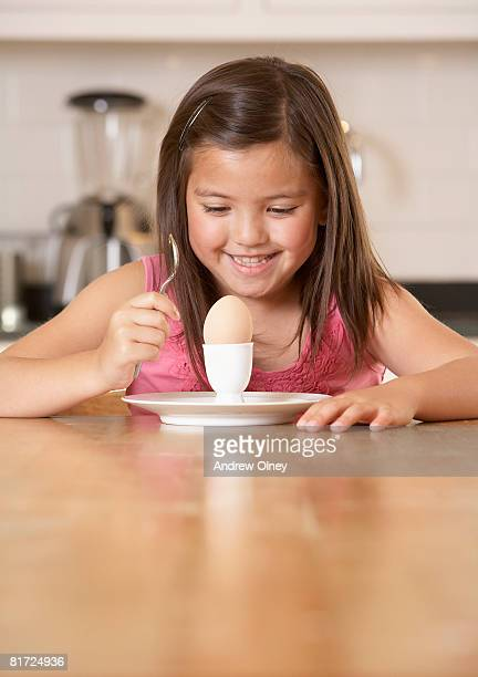 Young girl in kitchen with a boiled egg smiling