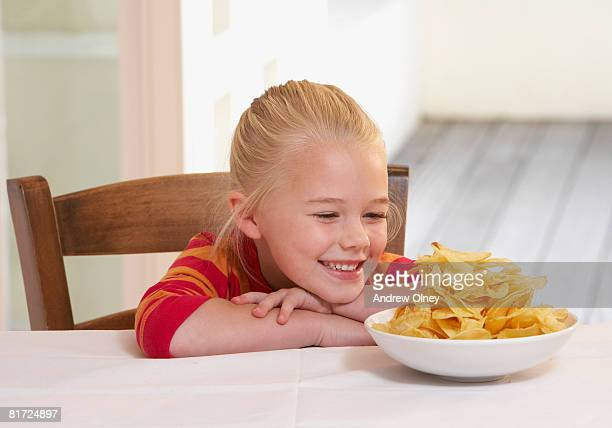 Young girl in kitchen with a bowl of potato chips smiling