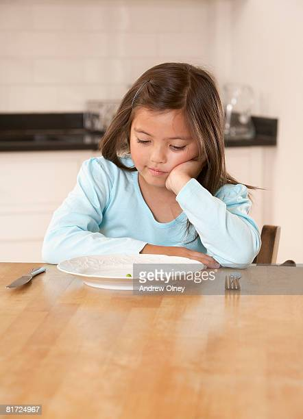 Young girl in kitchen with a single green pea on her plate looking unhappy