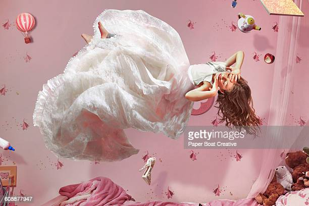Young girl in long white dress floating in bedroom