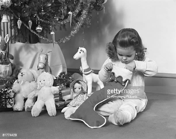 young girl in pajamas, opening christmas stocking next to christmas tree. (photo by h. armstrong roberts/retrofile/getty images) - noel noir et blanc photos et images de collection