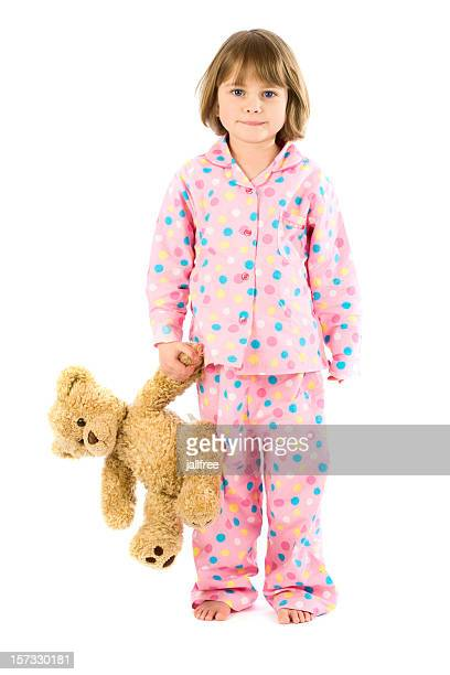 Young girl in pajamas with teddy bear on white