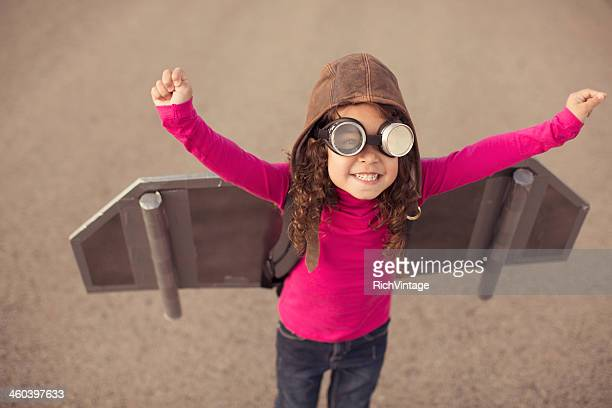 young girl in pilot gear with toy aircraft wings - aircraft wing stock pictures, royalty-free photos & images