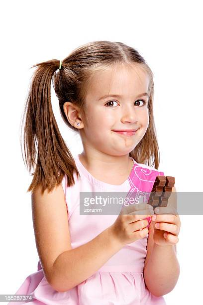 Young girl in pink dress holding chocolate bar