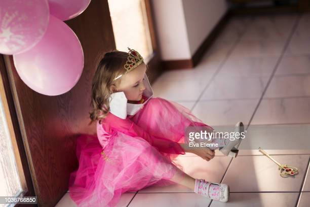 young girl in pink party dress putting on heeled shoes - princess stock pictures, royalty-free photos & images