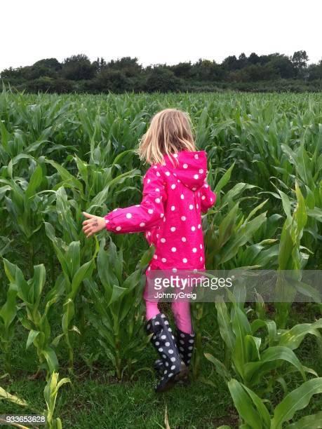 Young girl in polka dot mac walking through field