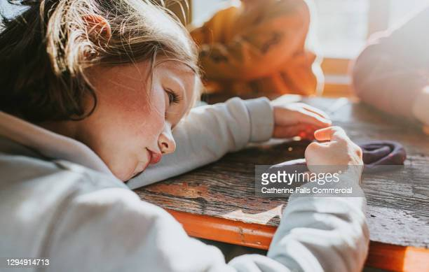 a young girl in preschool puts her head down on the desk and pouts - childhood stock pictures, royalty-free photos & images