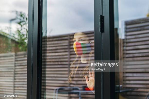 young girl in rainbow face mask by back door - sadness stock pictures, royalty-free photos & images