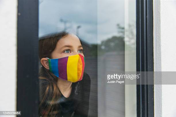 young girl in rainbow face mask looking through window - flatten the curve stock pictures, royalty-free photos & images