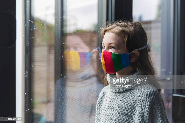 young girl in rainbow mask by window - caucasian ethnicity stock pictures, royalty-free photos & images