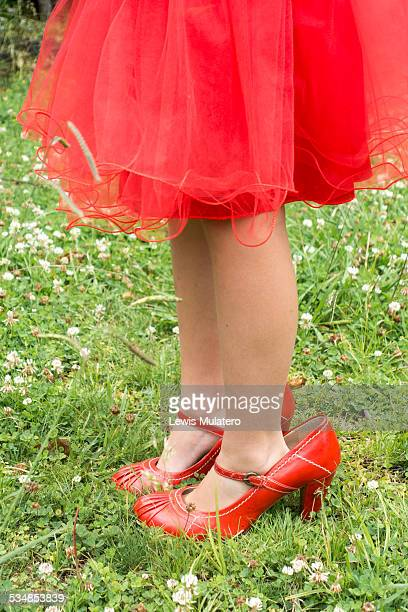 Young girl in red dress wearing mums shoes