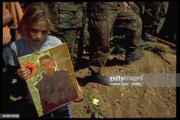 Young girl in Rogova, Kosovo, holds a photograph during the funeral of Kosovo Liberation Army soldier who was killed during the Yugoslavian Civil...