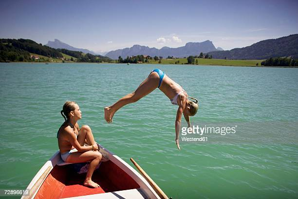 Teenage girls (13-15) sitting on boat, one jumping in water, side view