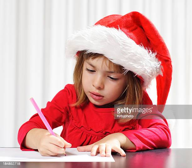 A young girl in Santa hat writes a note