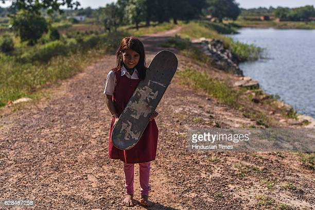 Young girl in school dress poses with her skate board on October 26, 2016 in Janwaar, India. Thanks to a German community activist and author Ulrike...