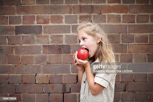 Young girl in school uniform eating an apple