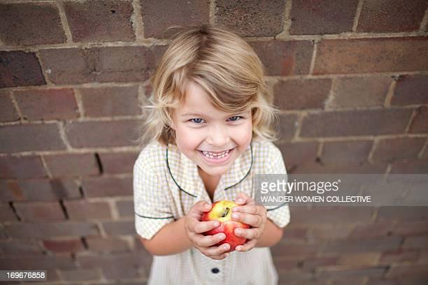 Young girl in school uniform eating apple