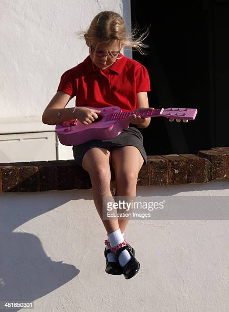 Young girl in school uniform sat on a wall playing a toy guitar Bude Cornwall UK