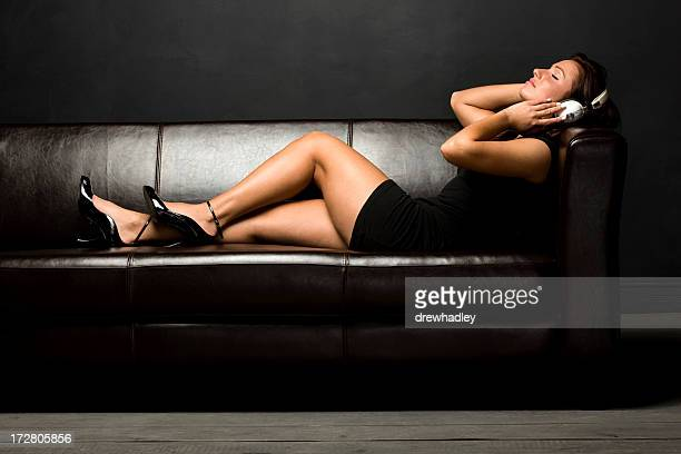 Young girl in short black dress with earphones on sofa.