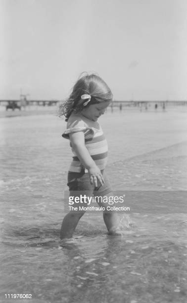 Young girl in striped swimming costume paddling in shallow water on an American beach with pier in the background circa 1924