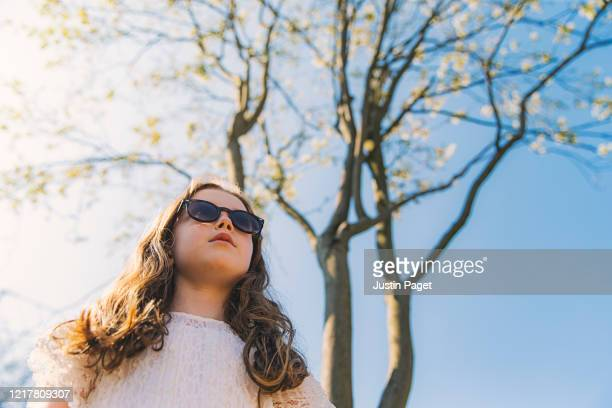 young girl in sunglasses under a blossoming tree - stiff stock pictures, royalty-free photos & images