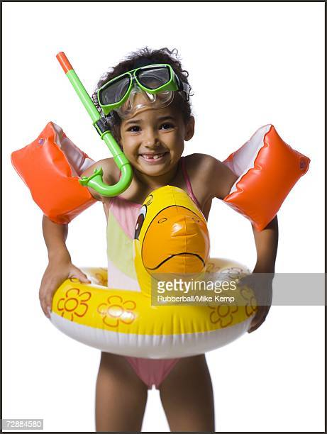 young girl in swimming gear smiles as she looks into the camera