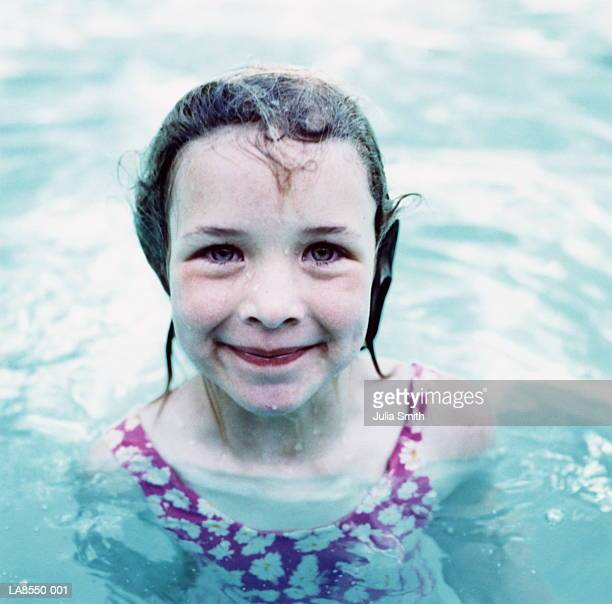 Young girl (5-7) in swimming pool, outdoors, portrait