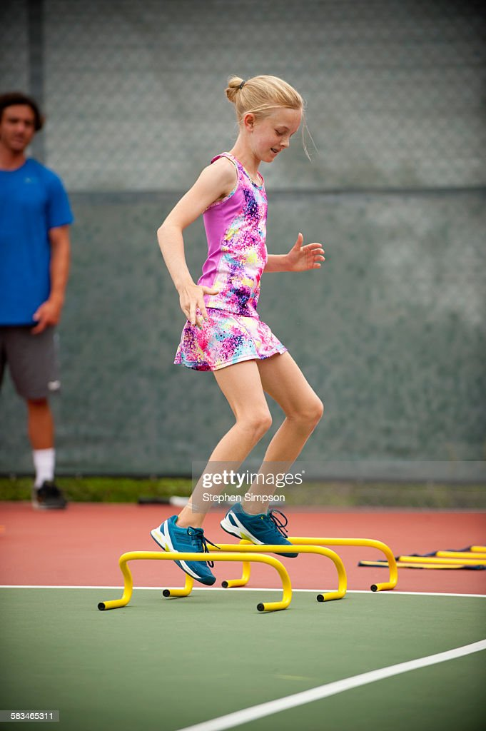young girl in tennis camp drills : Stock Photo