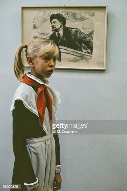 A young girl in traditional clothing stands in front of a framed print of Vladimir Lenin Russia September 1986