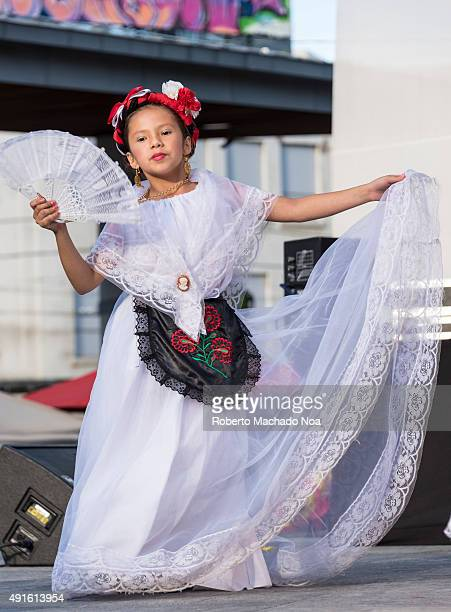 SQUARE TORONTO ONTARIO CANADA Young girl in white dress holding a handfan performing Flamenco folk dance on stage at MexFest 2015 in Toronto MexFest...