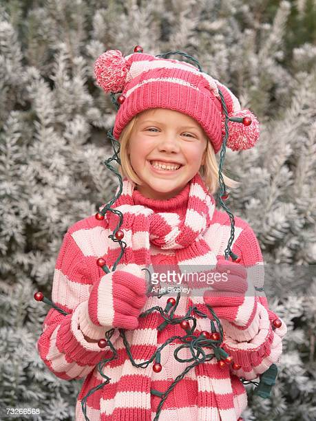 Young girl in winter clothing with Christmas lights