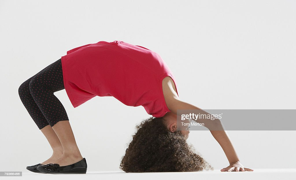 Young girl indoors doing back walkover : Stock Photo