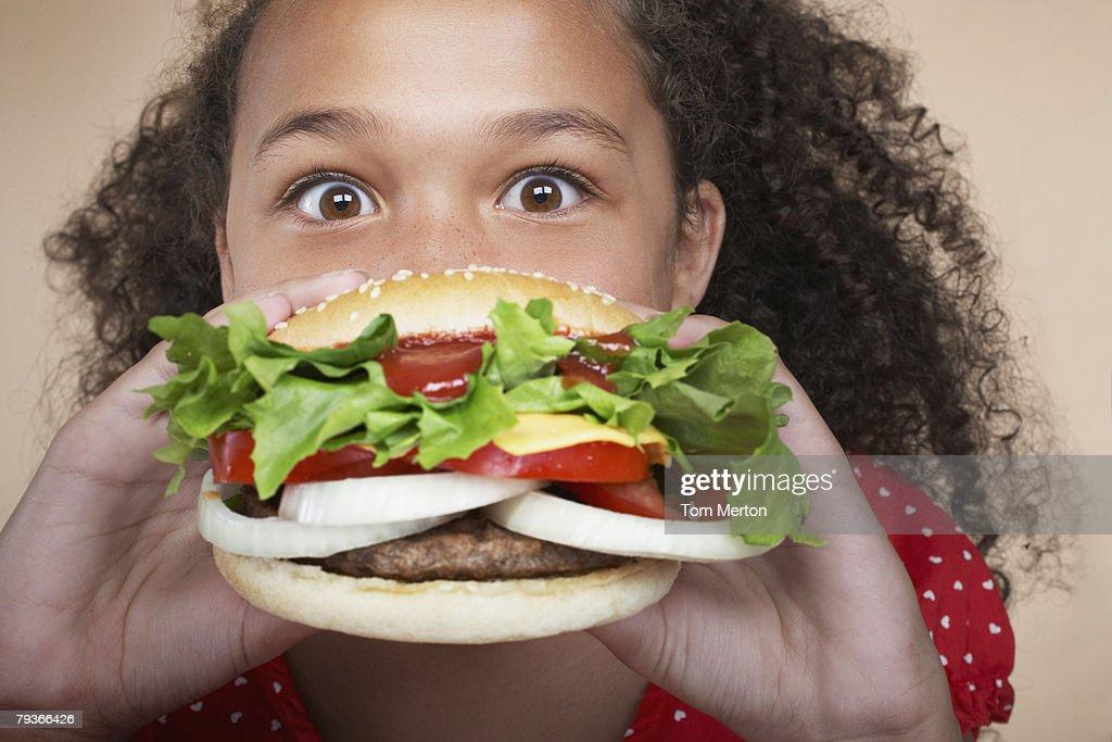 Young girl indoors eating a hamburger : Stock Photo