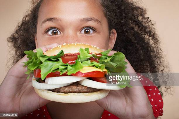 Young girl indoors eating a hamburger