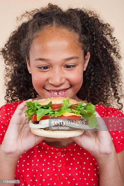 Young girl indoors looking a hamburger