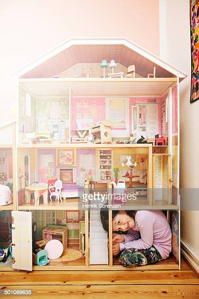 young girl inside a giant dollhouse