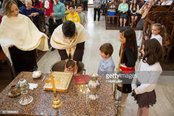 A young girl is baptized inside the Church of the Holy Cross