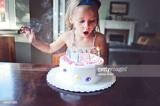 young girl is blowing out candles on birthday cake - birthday candles stock photos and pictures