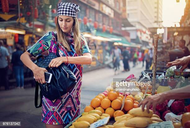 young girl is buying fruits and vegetables at the marketplace in the chinatown - malaysia beautiful girl stock photos and pictures