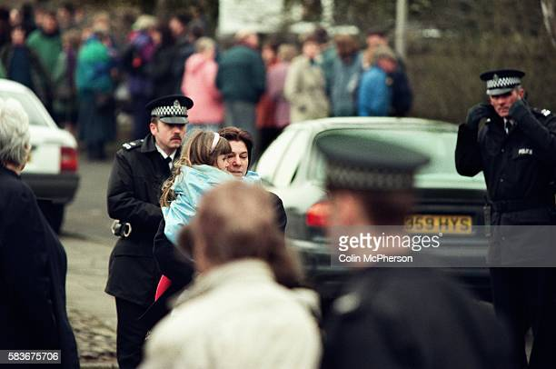 A young girl is carried away by an adult outside Dunblane primary school Scotland shortly after the shooting incident on the premises The Dunblane...