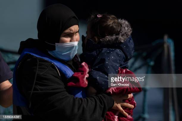 Young girl is carried by a migrant woman after arriving into Dover docks with Border Force on September 8, 2021 in Dover, England. The week has seen...