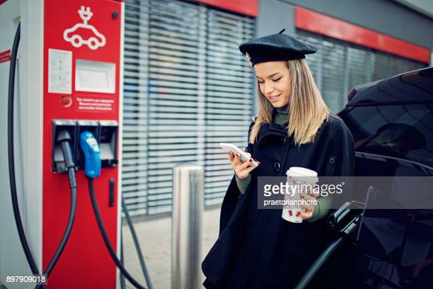 Young girl is charging her electric car at the charging station and texting