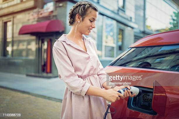 young girl is charging her electric car in the city - electric vehicle stock pictures, royalty-free photos & images