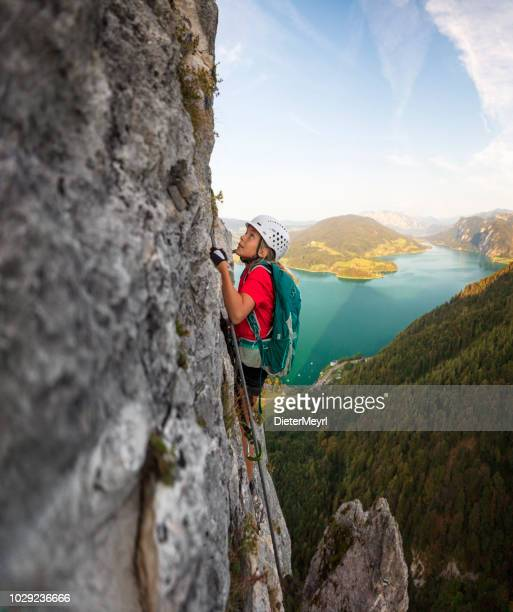young girl is climbing to the top of a mountain in alps - outdoor pursuit stock pictures, royalty-free photos & images