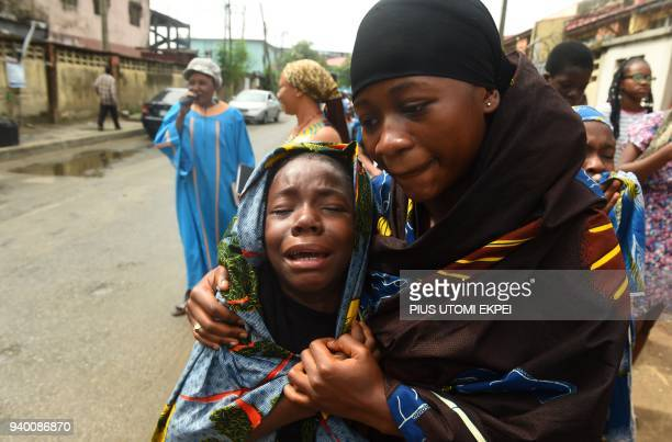 TOPSHOT A young girl is comforted as she cries during a dramatisation of the crucifixion of Jesus Christ to mark Good Friday heralding the start of...