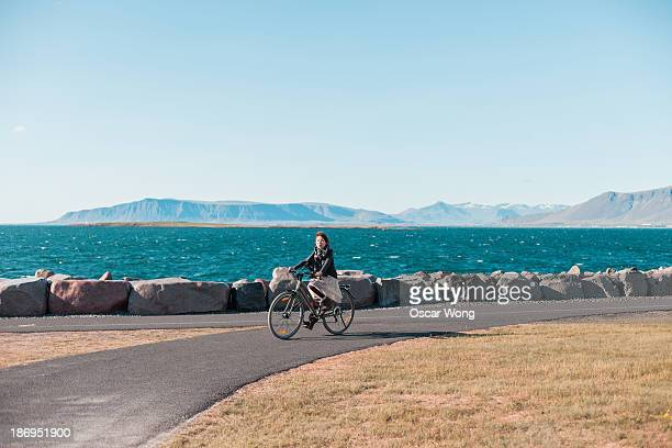 A young girl is cycling by the sea